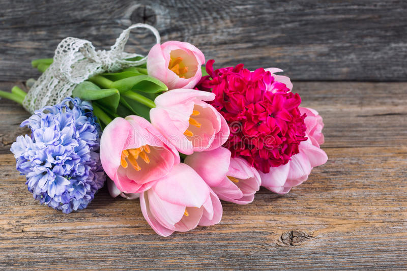 Bouquet of spring flowers decorated with ribbon on old wooden table. Soft focus stock photo