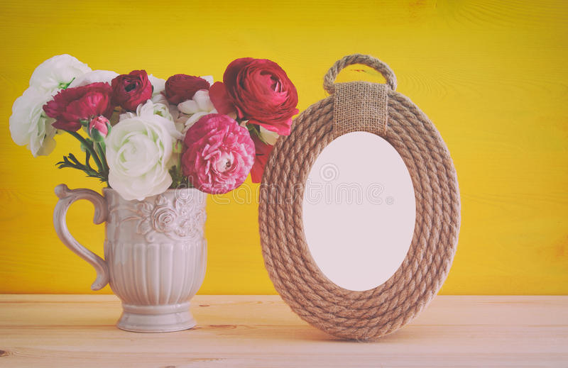 Bouquet of spring flowers next to blank vintage photo frame. Image of beautiful bouquet of spring flowers next to blank vintage photo frame on wooden table. For royalty free stock image