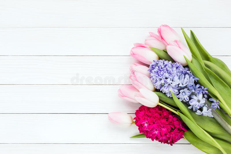 Bouquet of spring flowers on white wooden background. Top view stock image