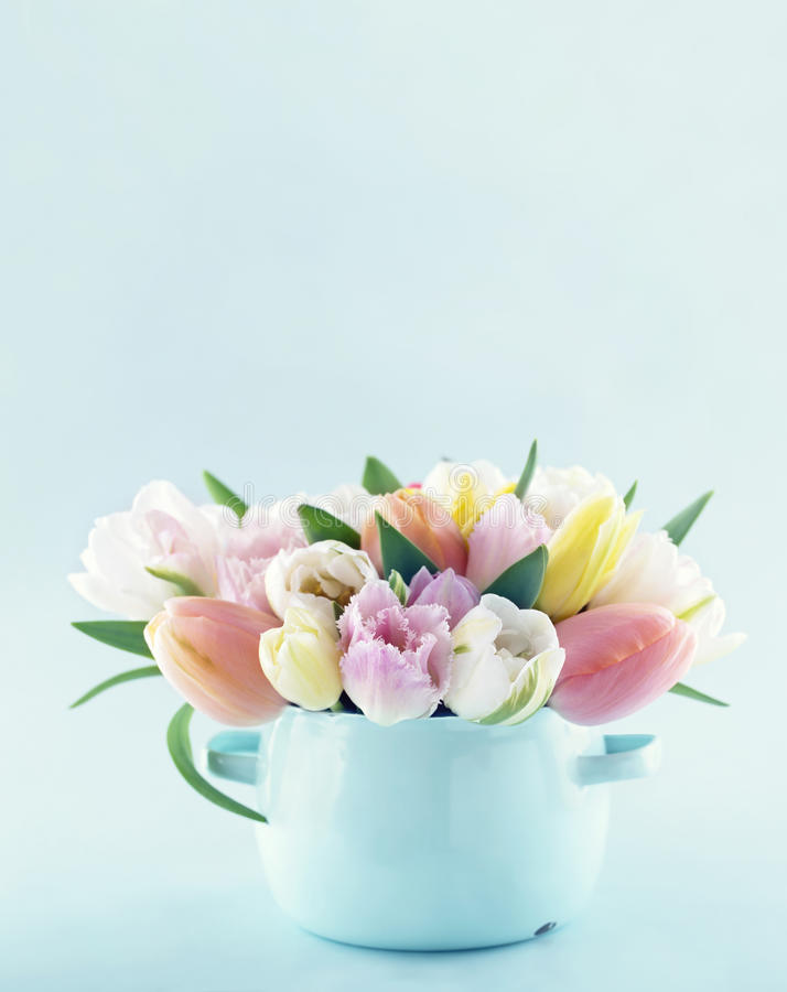 Bouquet of spring tulips. In a vintage vase on light blue pastel background with copy space stock photo