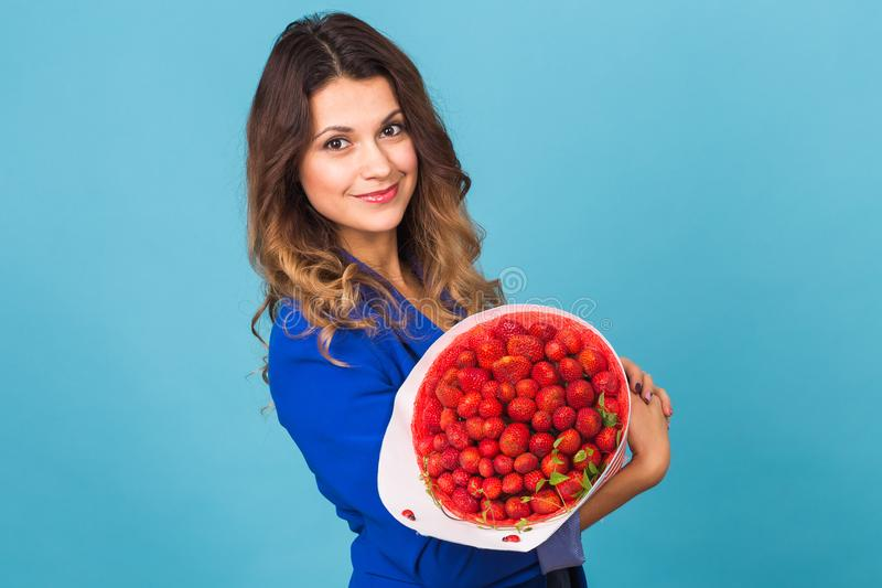 Bouquet of strawberries in the hands of a girl on blue background stock images