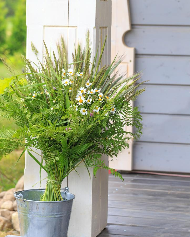 A bouquet of summer wild herbs and flowers in nature, the summer solstice. Summer sun celebration. Ligo in Latvia, Europe royalty free stock image