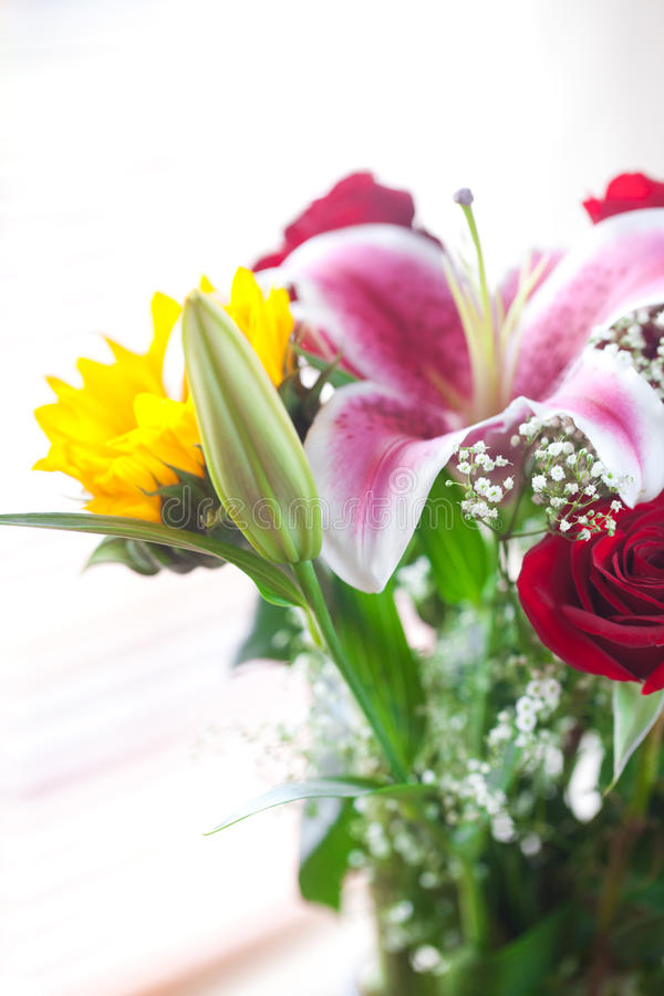 Bouquet of sunflowers, lily and roses in a vase royalty free stock image
