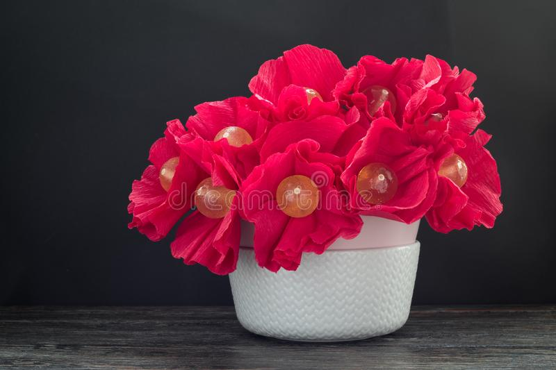 Bouquet of tasty lollipops in vase on wooden table. Candy flowers stock photography