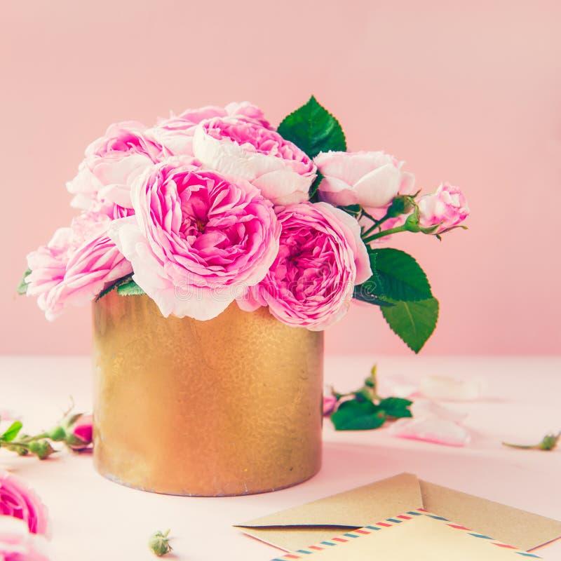 Bouquet tendre de roses de thé rose dans le pot de vintage, blanc de carte de voeux et enveloppe de papier de métier sur le fond  images libres de droits