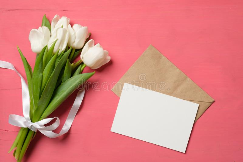 Bouquet of tulips and blank card with kraft envelope on pink desk background royalty free stock photo