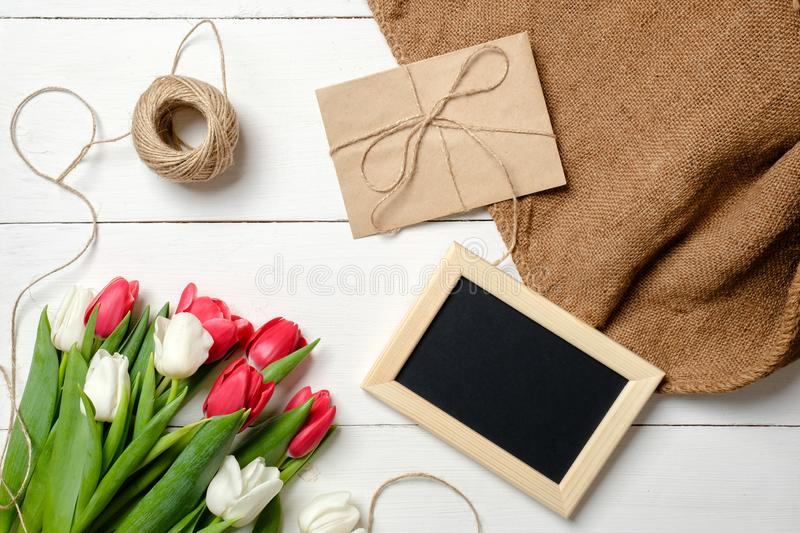 Bouquet of tulips flowers, blank picture frame, kraft envelope, twine, burlap on white wooden table. Vintage greeting card for wom royalty free stock photos