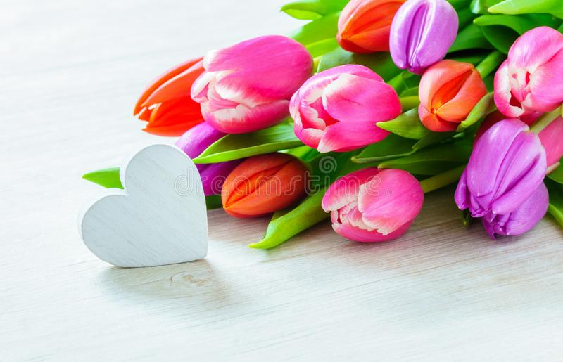 Bouquet of tulips and heart in front of spring scene stock images