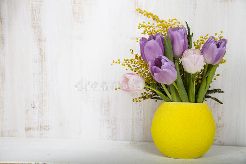 Bouquet of tulips and mimosa in a yellow vase on a wooden background. Still life with beautiful flowers on holiday stock image