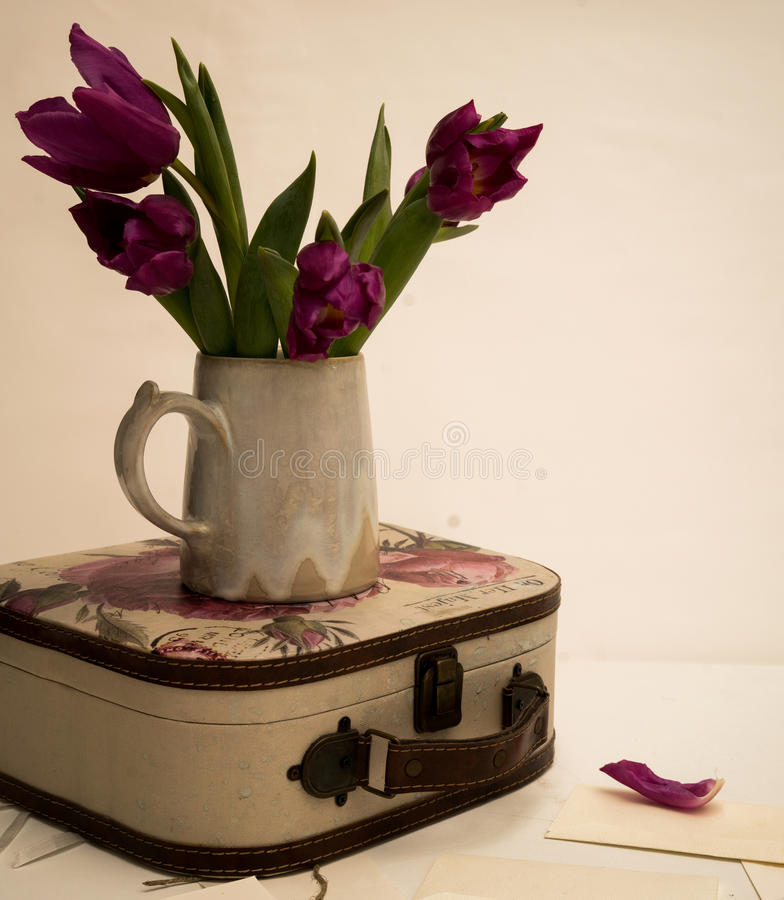 Bouquet of tulips and an old suitcase on the table, Provence, Shabby Chic royalty free stock image