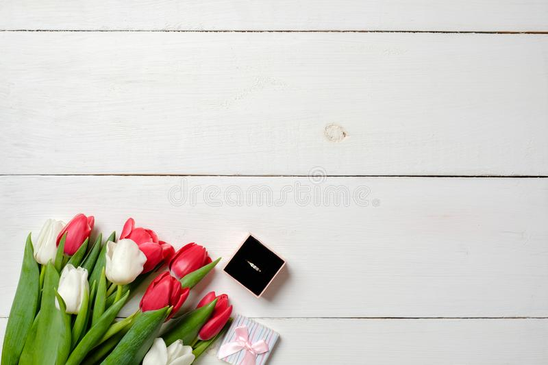 Bouquet of tulips and ring box on white wooden background. Marriage proposal, vintage wedding invitation card. Mockup with copy sp royalty free stock images