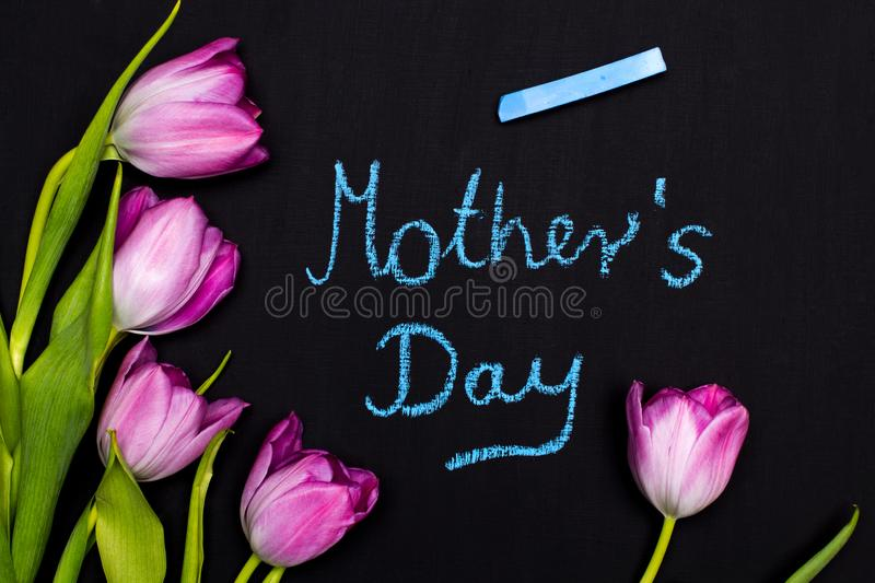 A bouquet of tulips and the sentence  MOTHER`S DAY written in chalk on a chalkboard stock images