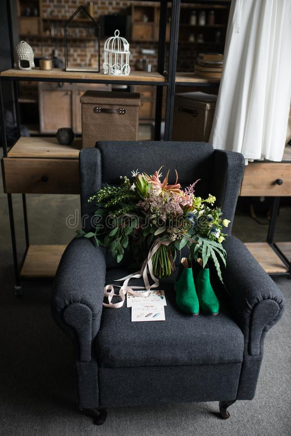 Bouquet vert riche de mariage avec les rubans roses sur le fauteuil gris Chaussures nuptiales vertes, et un mensonge élogieux de  photos stock