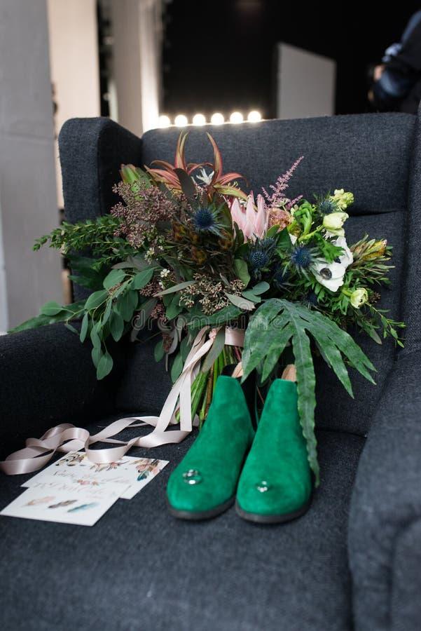 Bouquet vert riche de mariage avec les rubans roses sur le fauteuil gris Chaussures nuptiales vertes, et un mensonge élogieux de  photographie stock libre de droits