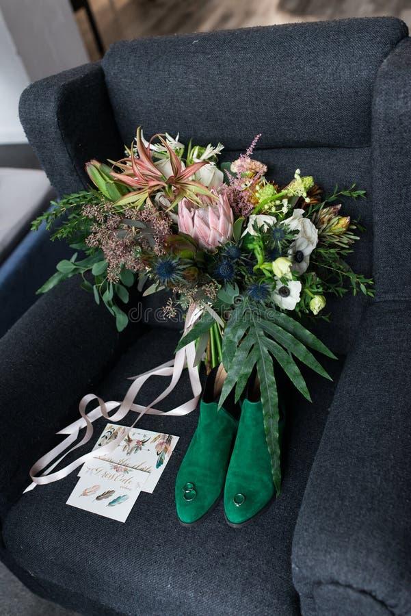 Bouquet vert riche de mariage avec les rubans roses sur le fauteuil gris Chaussures nuptiales vertes, et un mensonge élogieux de  photos libres de droits