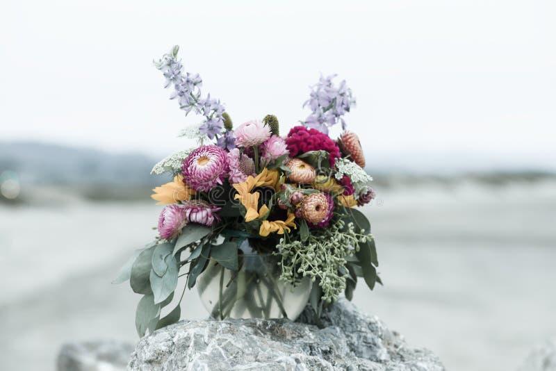 Bouquet von Mums, Eucalyptus und LIlacs auf einem Stone Rock in Half Moon Bay, Kalifornien lizenzfreie stockfotos