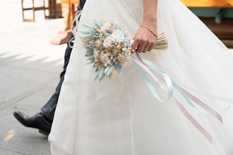Bouquet of wedding flowers in the hands of the bride in a white long dress. Background, bridal, girl, love, beautiful, beauty, celebration, day, decoration royalty free stock photo