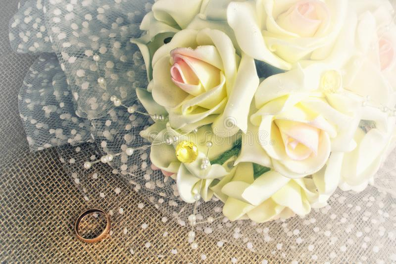 Bouquet and wedding ring of the bride on burlap royalty free stock photography
