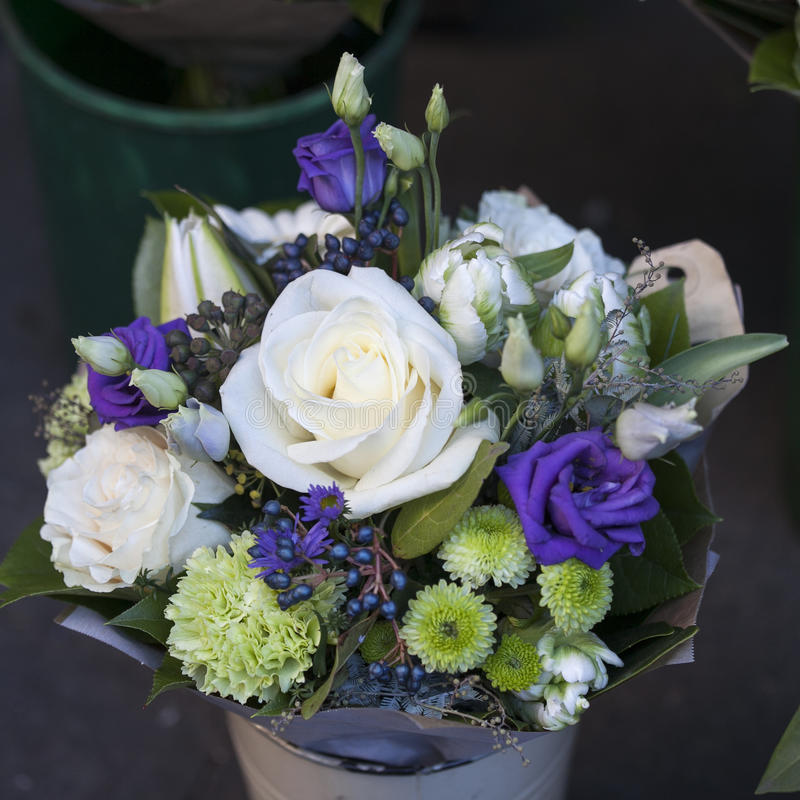 Bouquet of white and blue roses with lisianthus chrysanthemum in an aluminum bucket. Bouquet of white and blue roses with lisianthus and chrysanthemum in an stock images