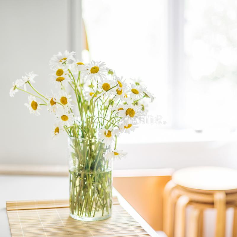 A bouquet of white daisies in a vase on the kitchen table against the background of a window, a refrigerator and stools. With a strong blur royalty free stock photos