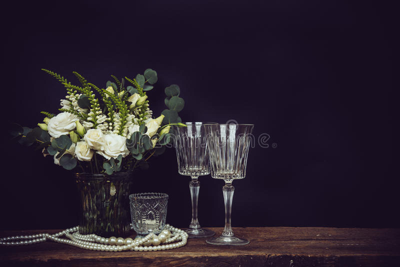 bouquet of white flowers, pearl beads and wine glasses on a black chalkboard background royalty free stock image