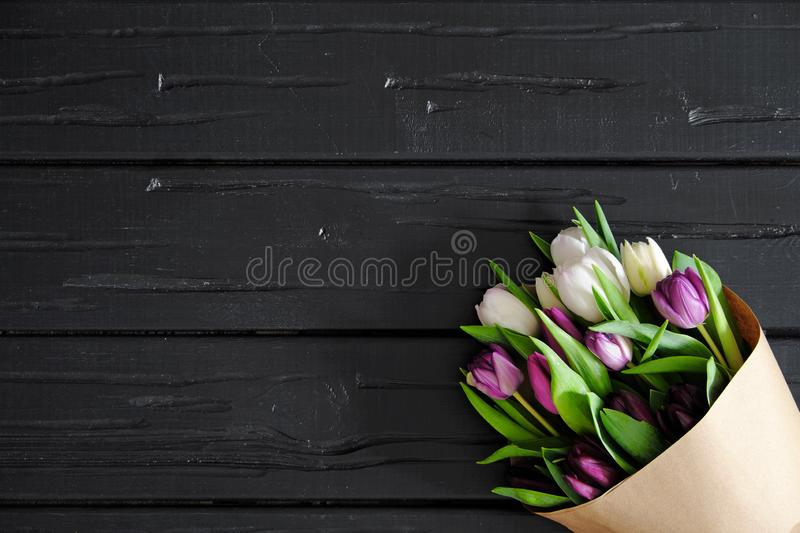 A bouquet of white and pink tulips in craft paper, on a black wooden background, flat lay. royalty free stock photo