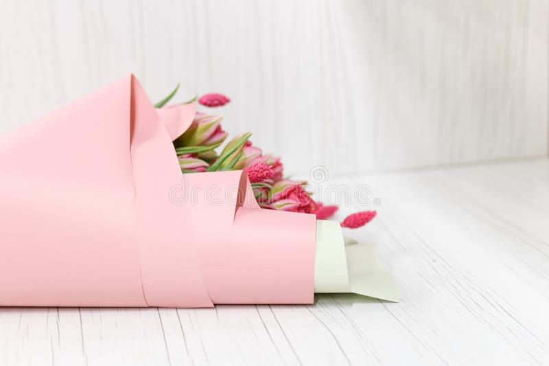 Bouquet of white and pink tulips wrapped by pink paper laying on white wooden table. Copy space. International women`s stock images