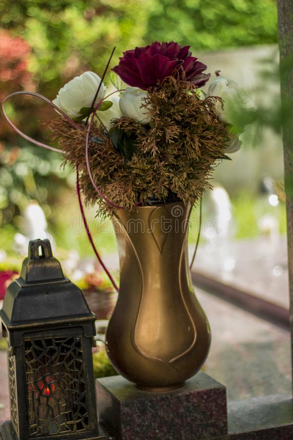 A bouquet of flowers in a gold vase and a candle at the cemetery for the days of all the saints. A bouquet of white and red flowers in a beautiful golden vase stock photos