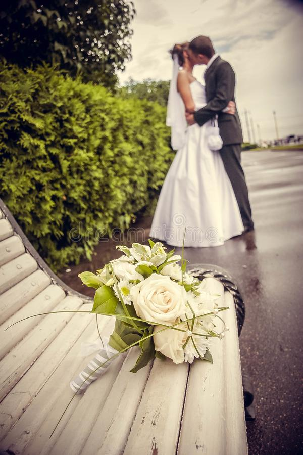 A bouquet of white roses against the backdrop of a kissing newlywed couple royalty free stock images