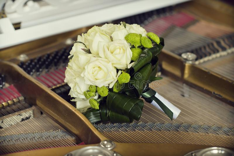 Bouquet of white roses for the bride on the piano stock photo