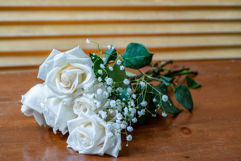 Bouquet of white roses with green leaves and small white flowers. The plant is a bouquet of white roses with green leaves and small white flowers, lying on an royalty free stock photo