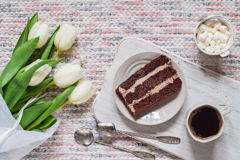 Bouquet of white tulips, coffee and chocolate cake. On textile background stock image