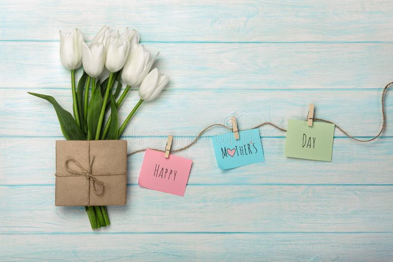 A bouquet of white tulips and envelope with a color stickers with clothespins on a rope and blue wooden boards . Mother`s day stock image