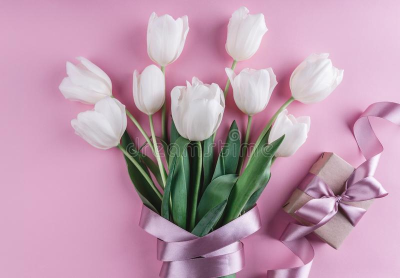 Bouquet of white tulips flowers with gift over pink background. Greeting card or wedding invitation stock photography