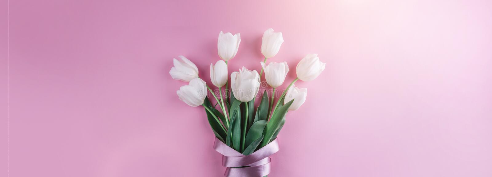 Bouquet of white tulips flowers on pink background. Card for Mothers day, 8 March, Happy Easter. Waiting for spring. Greeting card or wedding invitation. Flat stock images