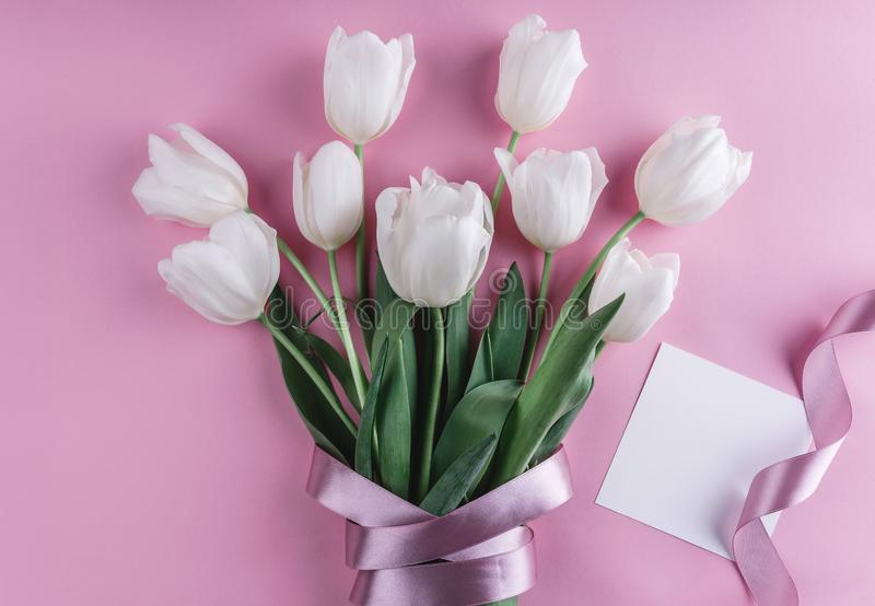 Bouquet of white tulips flowers and sheet of paper over light pink background. stock images