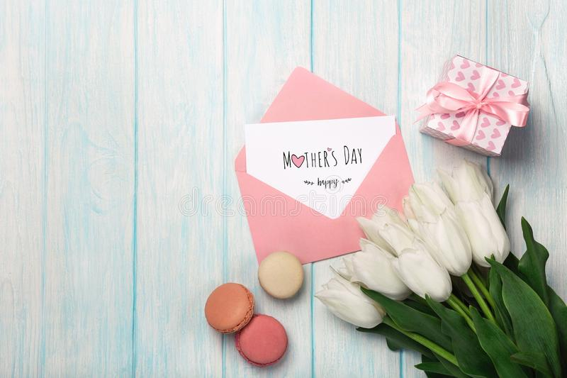 A bouquet of white tulips with a gift box, macarons, love note and color envelope on blue wooden boards . Mother`s day. A bouquet of white tulips with a gift box stock photography