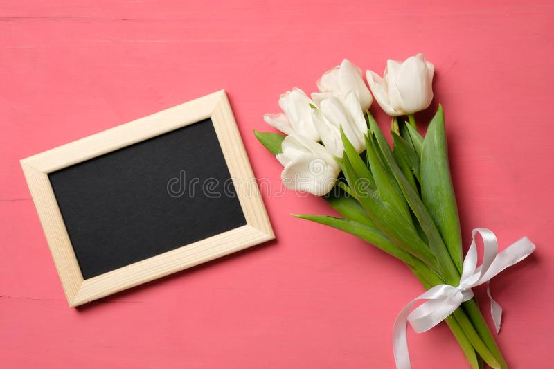 Bouquet of white tulips and photo frame with copy space for congratulation text on pink wooden background, banner mockup for Woman stock photography