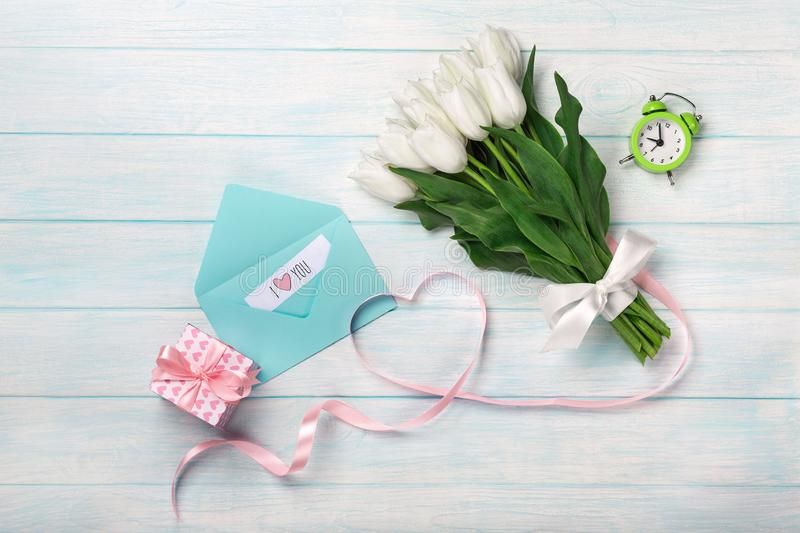 A bouquet of white tulips and a pink ribbon in the form of a heart with a gift box, love note and color envelope on blue wooden royalty free stock image