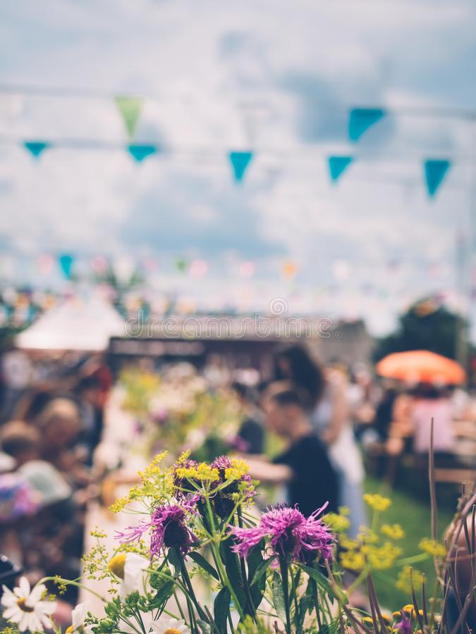 Bouquet of wild flowers on the table at summer festival. Bouquet of wildflowers, people sitting at wooden tables, colourful flags and bright clouds on background royalty free stock photo