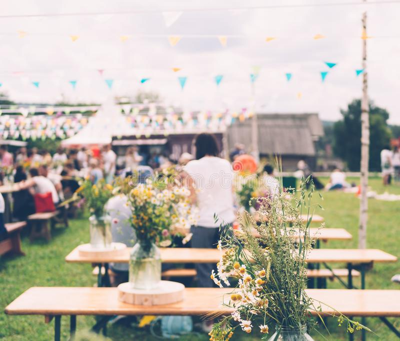 Bouquet of wild flowers on the table at summer festival. Wooden tables on green lawn at summer country festival royalty free stock photos