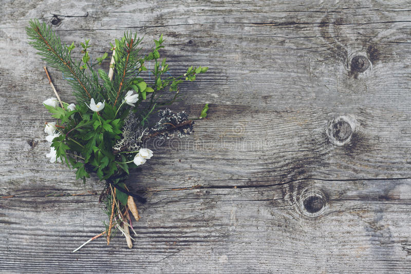 Bouquet of wild forest flowers. Horizontal front view of bouquet of wild forest flowers with green leaves and tree sticks on wooden background copyspace royalty free stock photo