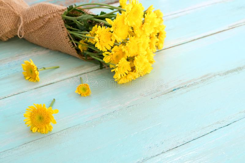 Bouquet of yellow chrysanthemum on blue wooden background. stock image