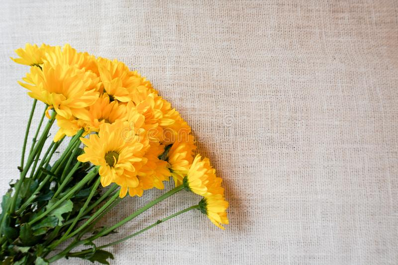 A bouquet of yellow flowers on a burlap backgound. For holiday celebrations like Mother`s Day, anniversary, birthday, springtime stock images
