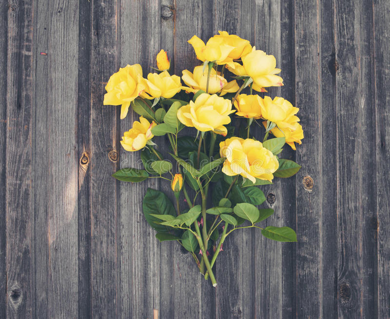 Bouquet of yellow garden roses on rustic weathered wooden backgr. Ound. Valentine`s Day and Mother`s Day background. Top view stock photos