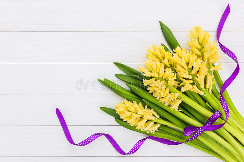Bouquet of yellow hyacinths decorated with purple ribbon. Top view stock photo