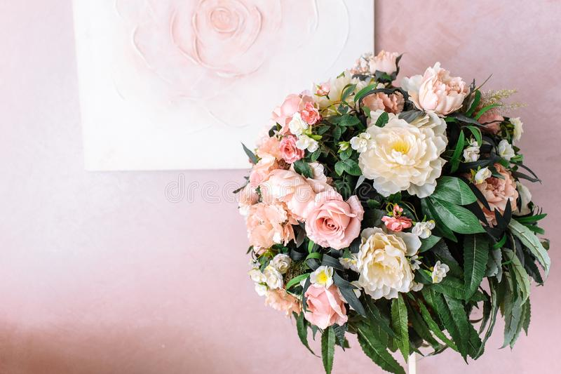Bouquet of yellow and pink flowers against the background of the image of a rose on a pink wall royalty free stock image