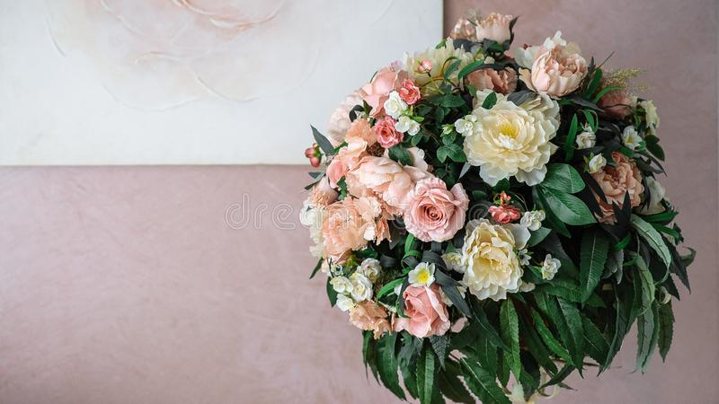 bouquet of yellow and pink flowers against the background of the pink wall stock photos