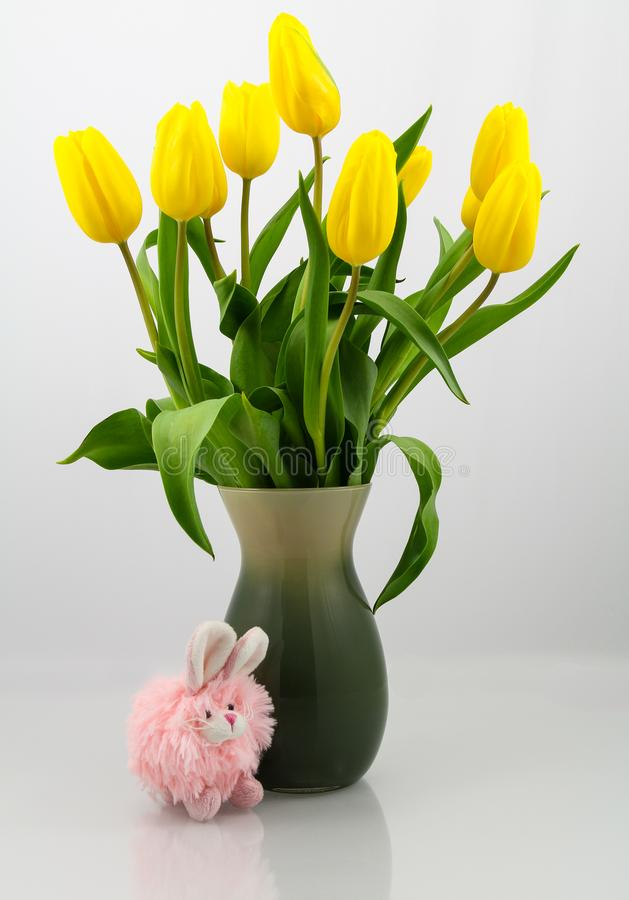 Bouquet of yellow tulips in a pleasing green vase isolated on a pale background. Pink bunny accents the base of the vase. stock photos