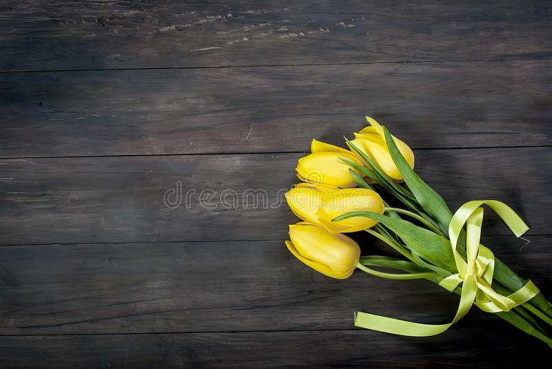 bouquet of yellow tulips with a yellow ribbon on a wooden background royalty free stock photos